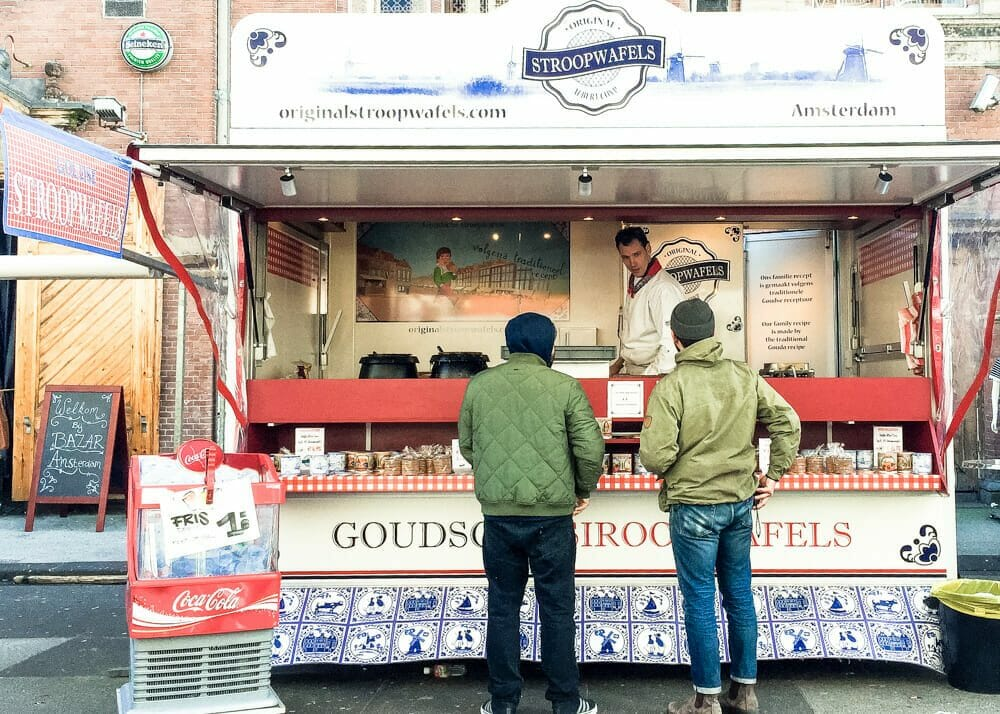 Two people in front of a confectionary trailer on a rainy Amsterdam Day