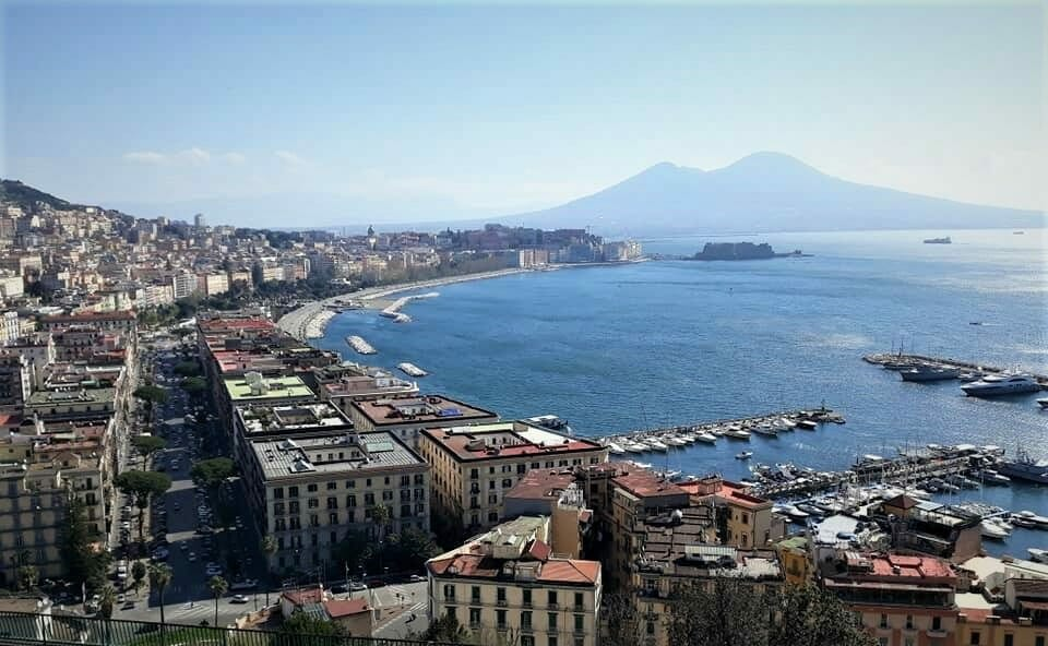 Blue waters of the Bay of Naples gracing the shores with the surrounding buildings admiring it from their peaceful place