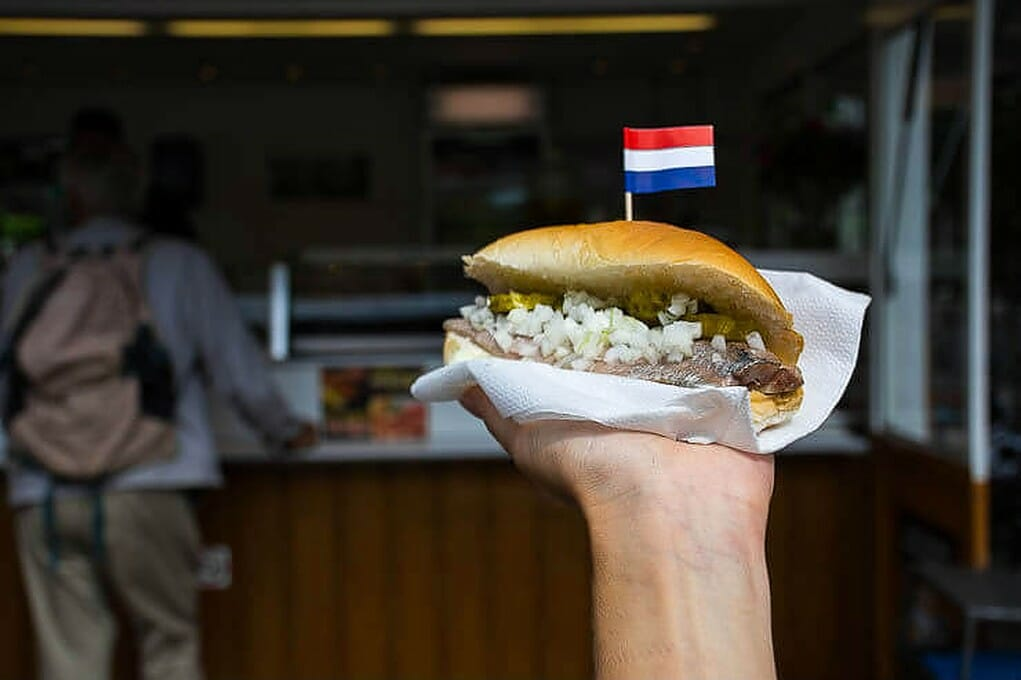 Man holding a herring sandwich with onions and topped with the flag of Holland