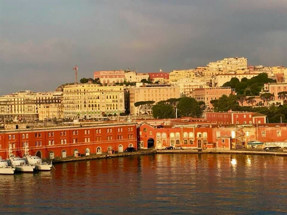 Coastal view of Naples, Italy with the warm colored buildings gracing the shores near the bay as the sun rises
