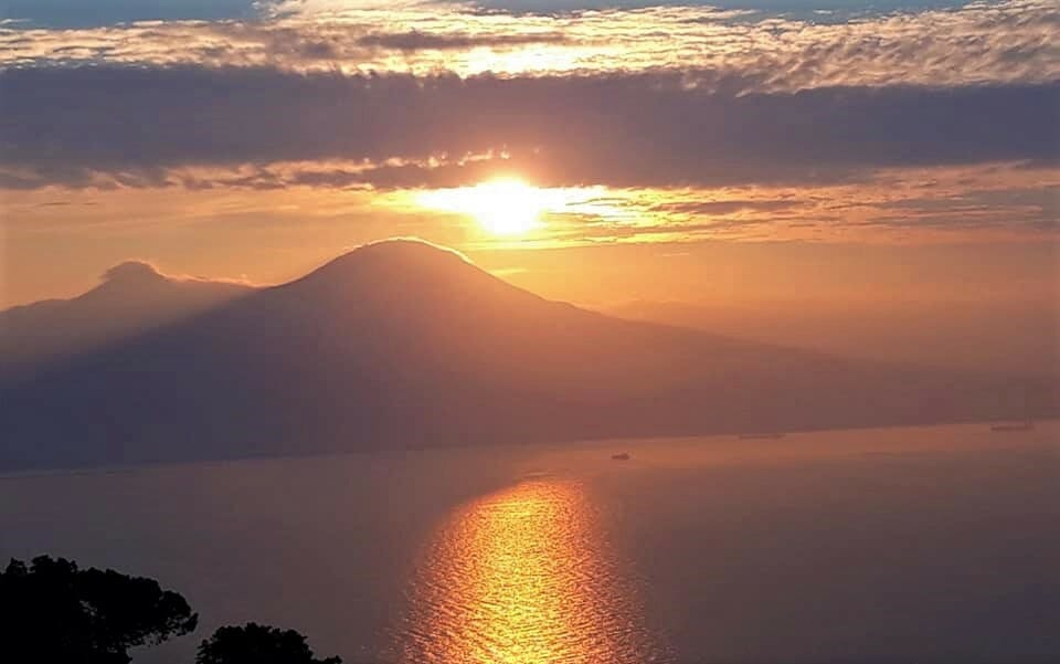 Sun setting over Mt. Vesuvius while the water reflects the light back gracefully