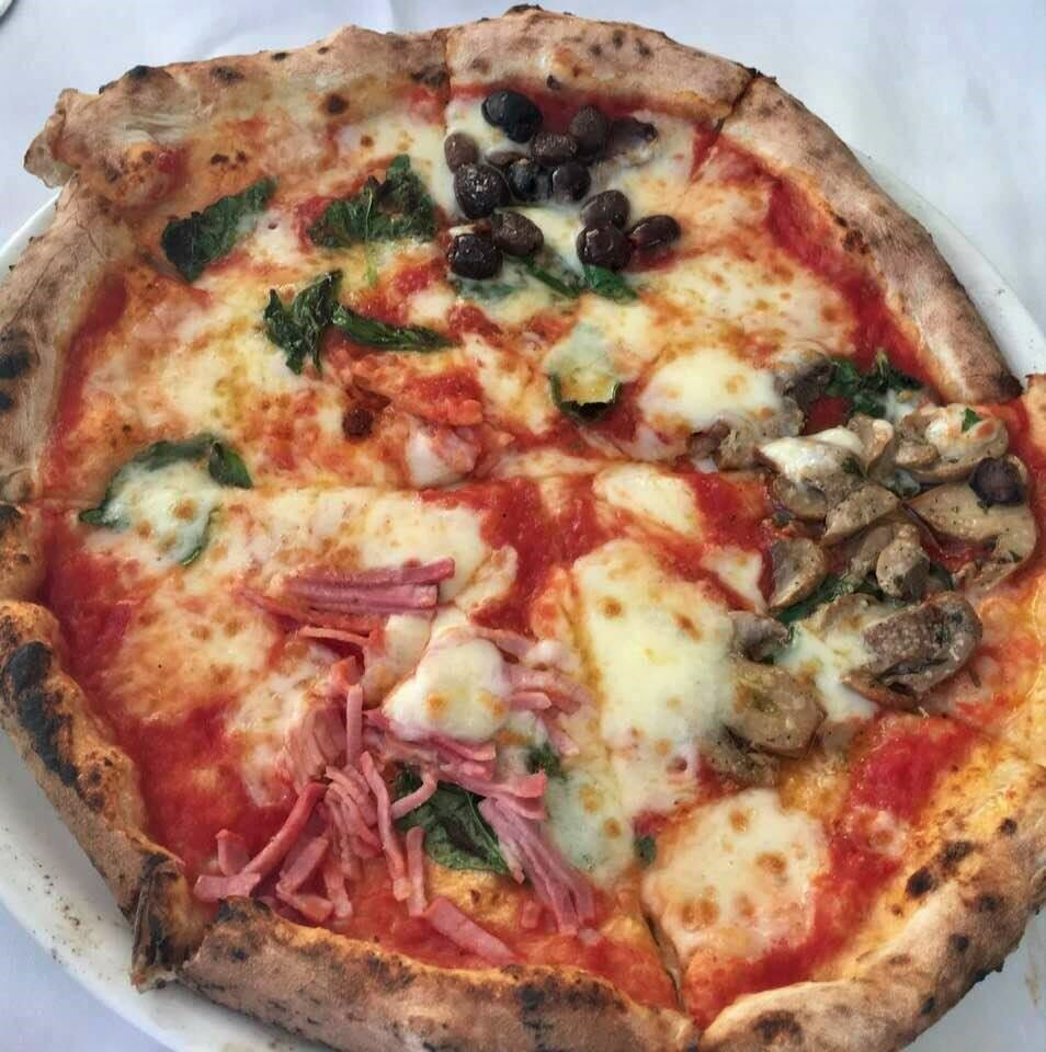 Pizza divided into four parts with olives, mozzarella, ham, basil, and mushrooms