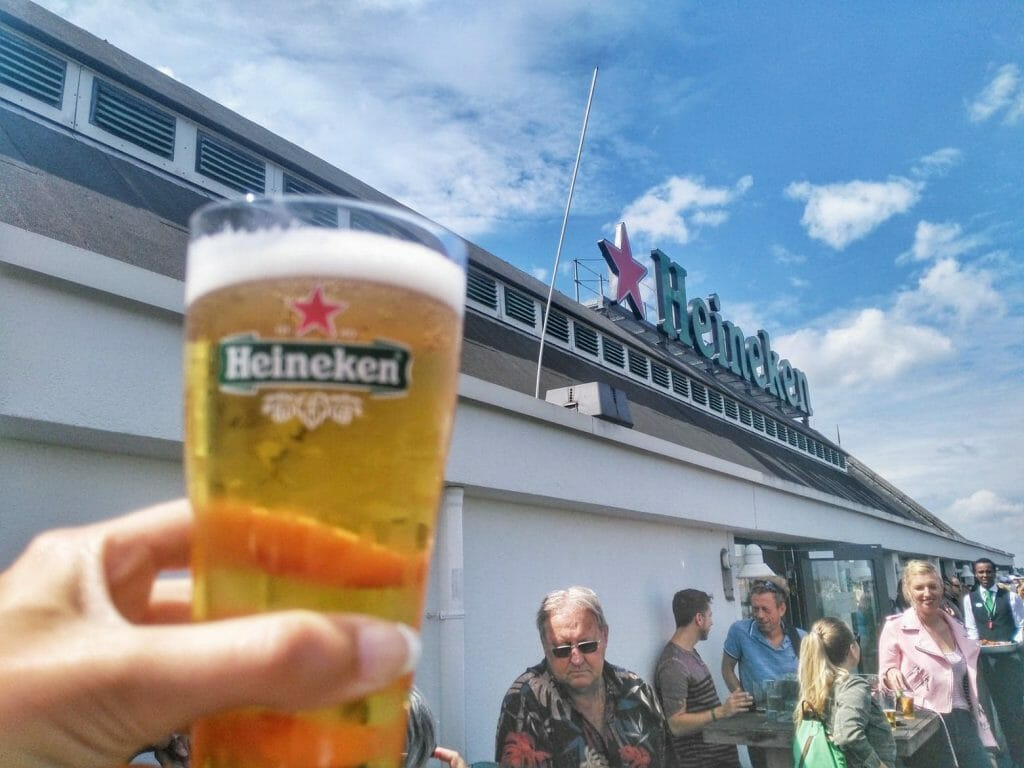 Man holding up a glass of Heineken up to the Heineken bulding