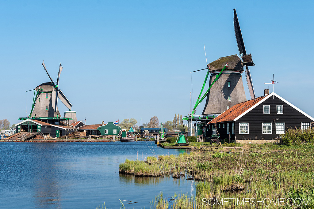 River by towering, old windmills on a sunny day