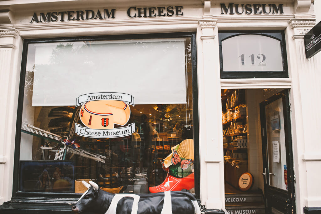 Front window of the Cheese Museum with the door open, white trimming, and a cheese sticker on the window