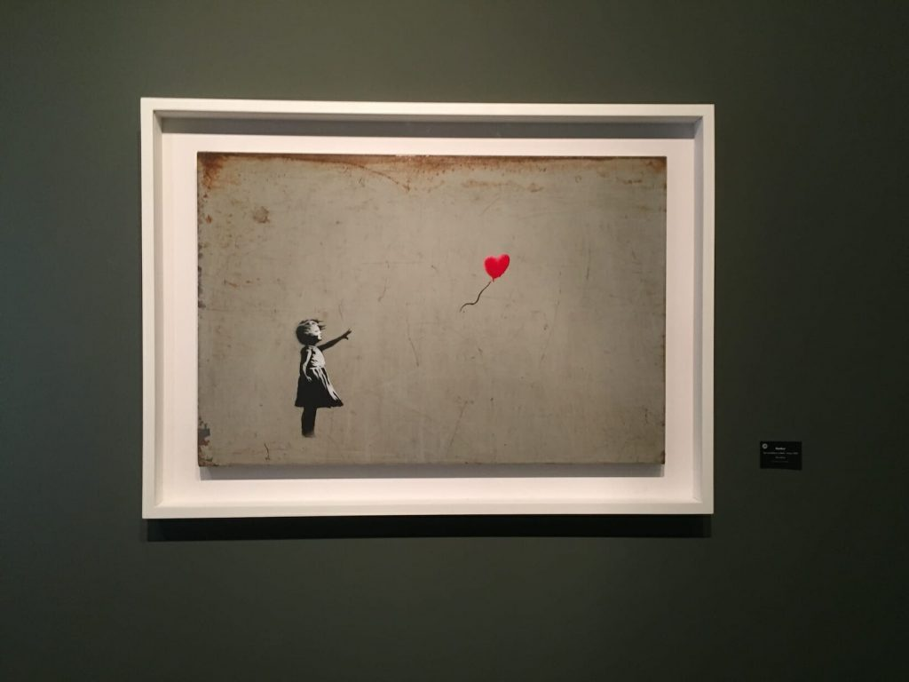 Painting of a little girl in black and white reaching for a red heart balloon thats floating away