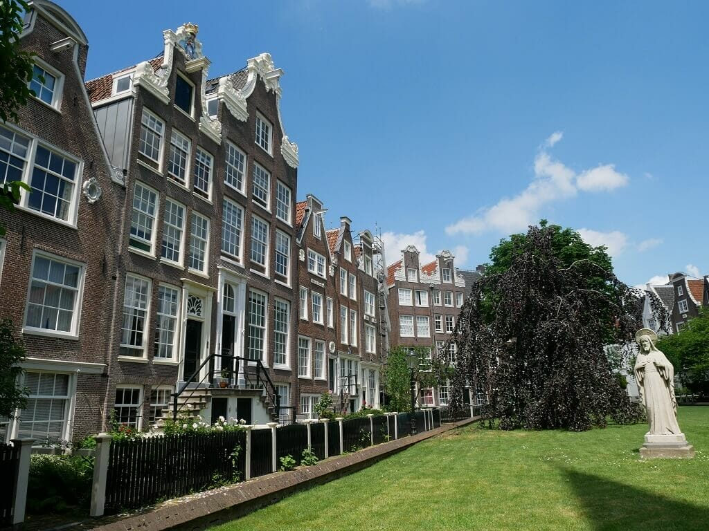 On a bright sunny Amsterdam day, Begijnhof houses are lined peacefully along the neat lawn