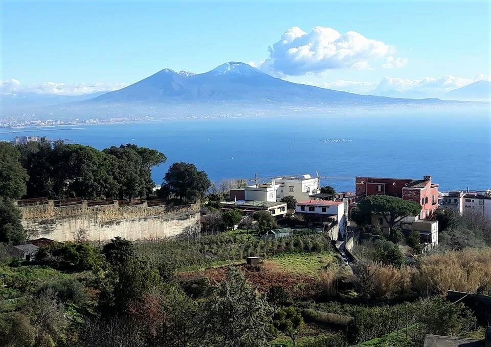 From a hill, the village below sits quiet with Mt. Vesuvius in the distance
