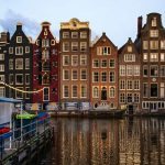 Long, narrow buildings clustered together facing the canals