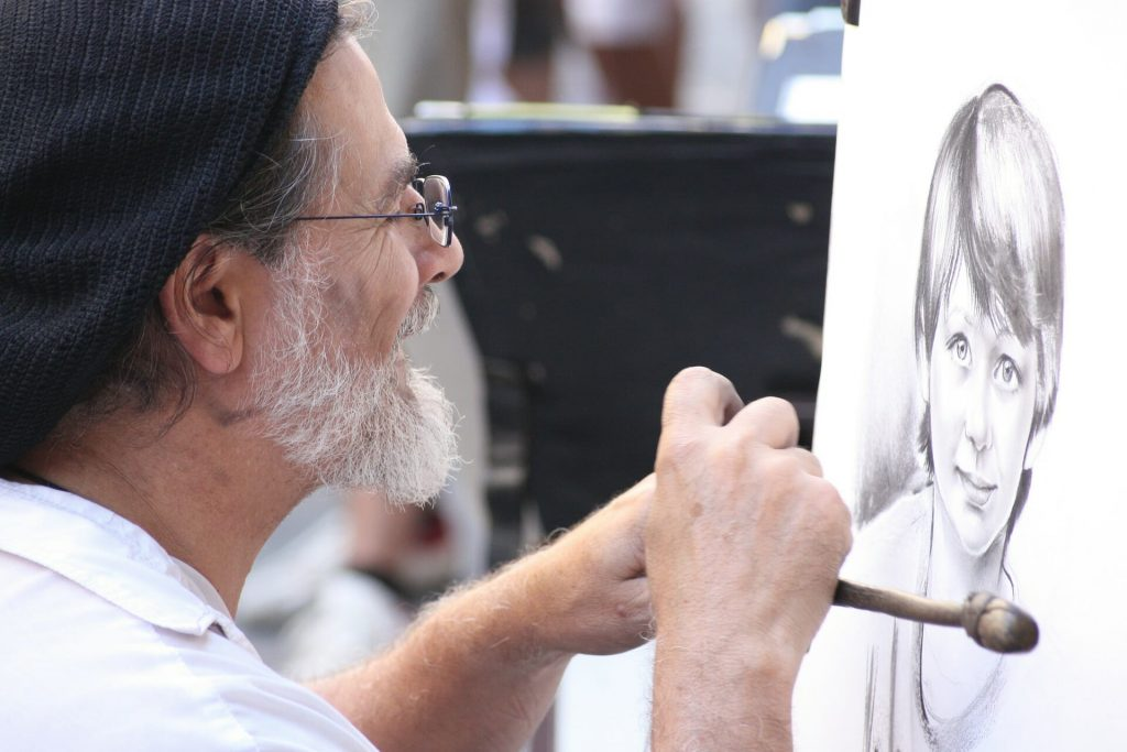 Man with a snow white beard and glasses drawing a picture of a young boy with a small smile on his face