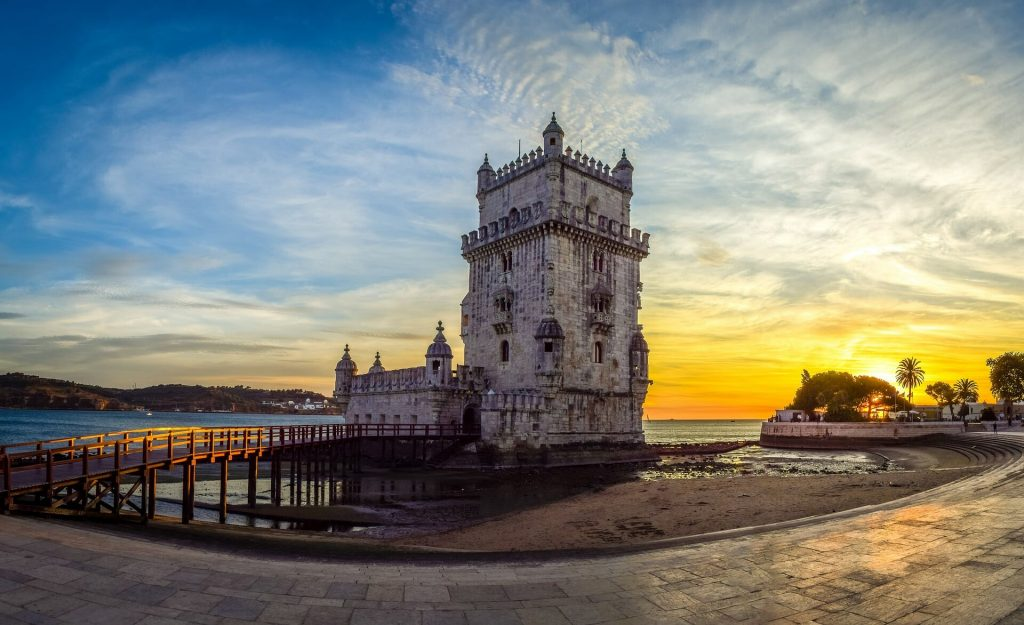 Ancient Belem Tower in Lisbon, Portugal while the sun sets over the water in the background