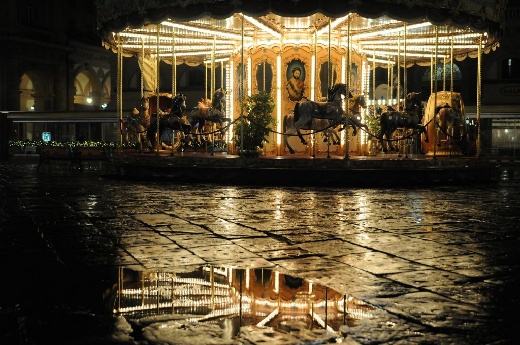 Carousel brightly light up and lively at night after a heavy rain
