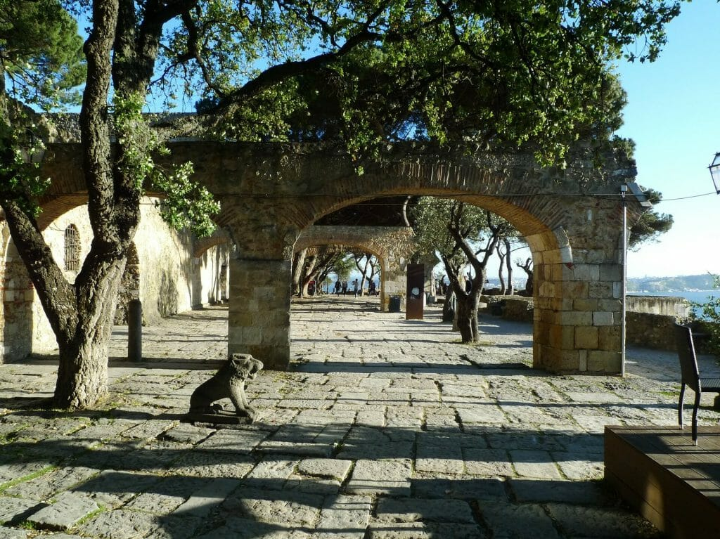 The courtyard of Sao Jorge Castle filled with trees, archways, and lion statues all around