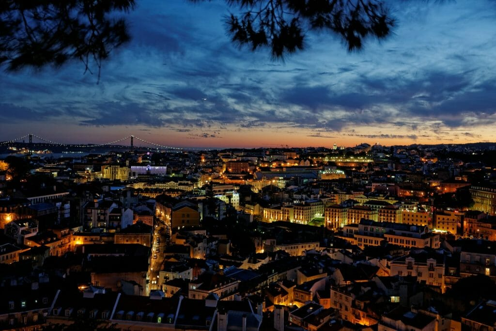 In the late evening, as the sun is done setting, the lights of Lisbon begin their glow as night life starts to thrum