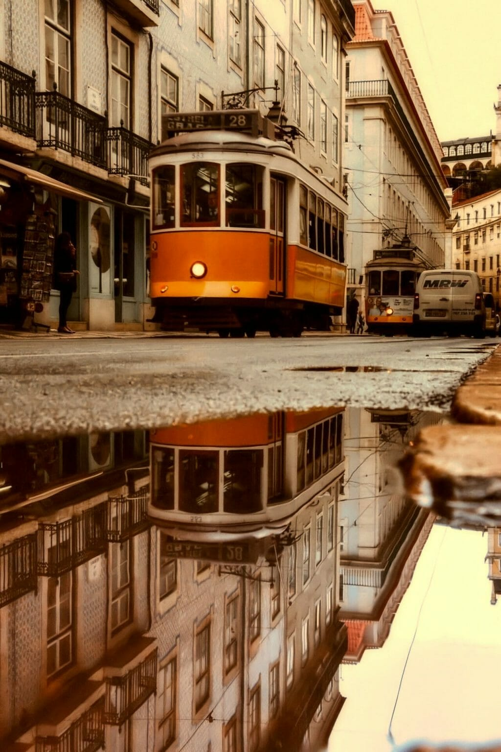 Big puddle in the ground reflecting an orange trolley car in a backstreet in Lisbon