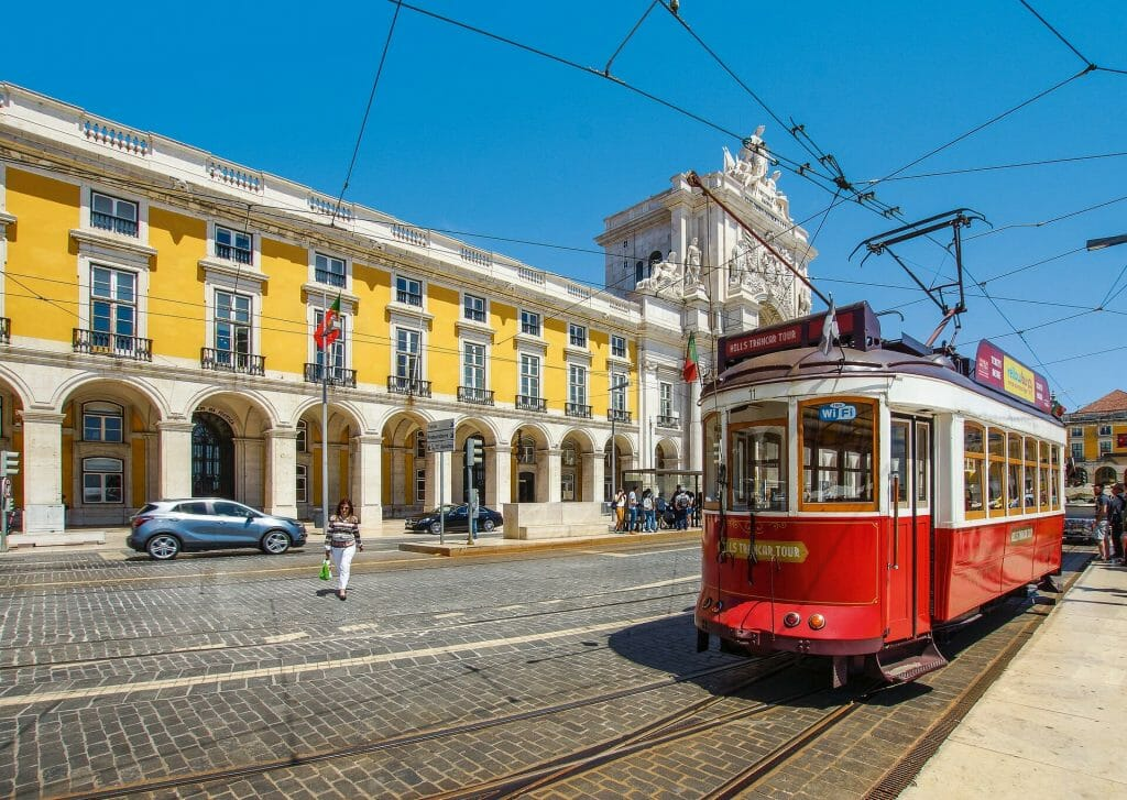 Sunny day in Lisbon with the trolley coming up the street and passed a yellow building