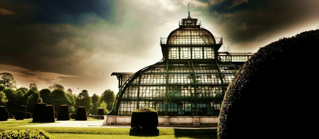 A greenhouse silhouette with a peaceful light surrounding it and the garden perimeter