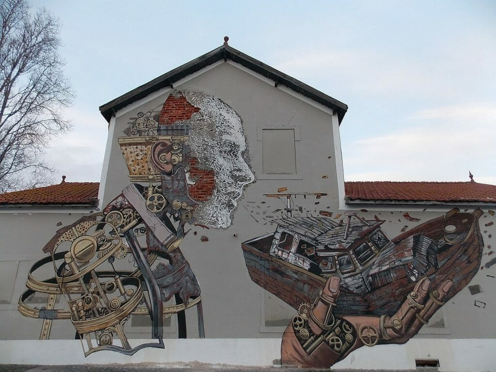Mural of a man blowing on a broken boat in the streets of Lisbon
