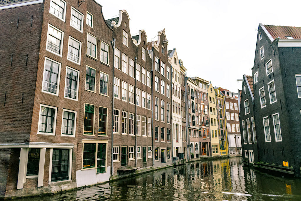 Long, narrow mild colored buildings on a wet Amsterdam street