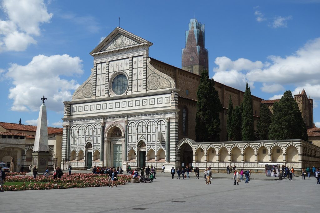 On a sunny day in Florence, visitors file in and out of the Santa Maria Novella with it's sleek black and white architecture