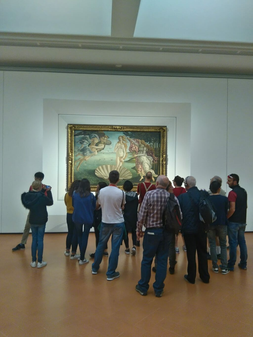 People gathering around the Birth of Venus painting in the Uffizi Gallery in Florence