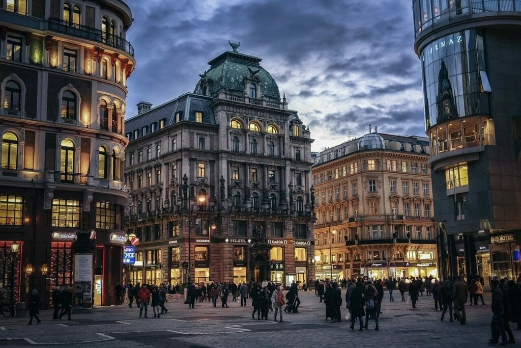 Calmly lit Vienna town with people humming around to get places