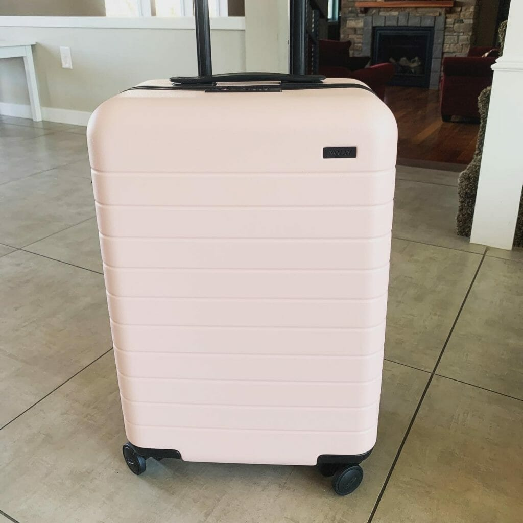 Pink hard shelled carry on on a tiled floor, ready for travel