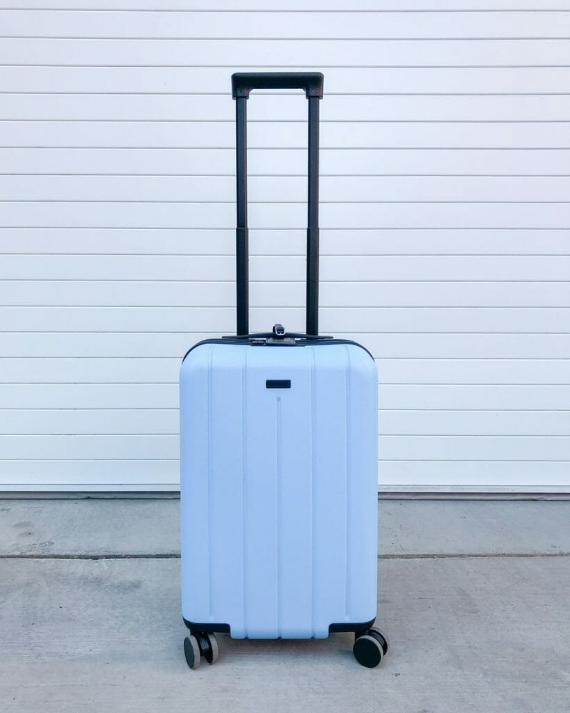 White spinner carry on outside on the concrete in front of white paneling