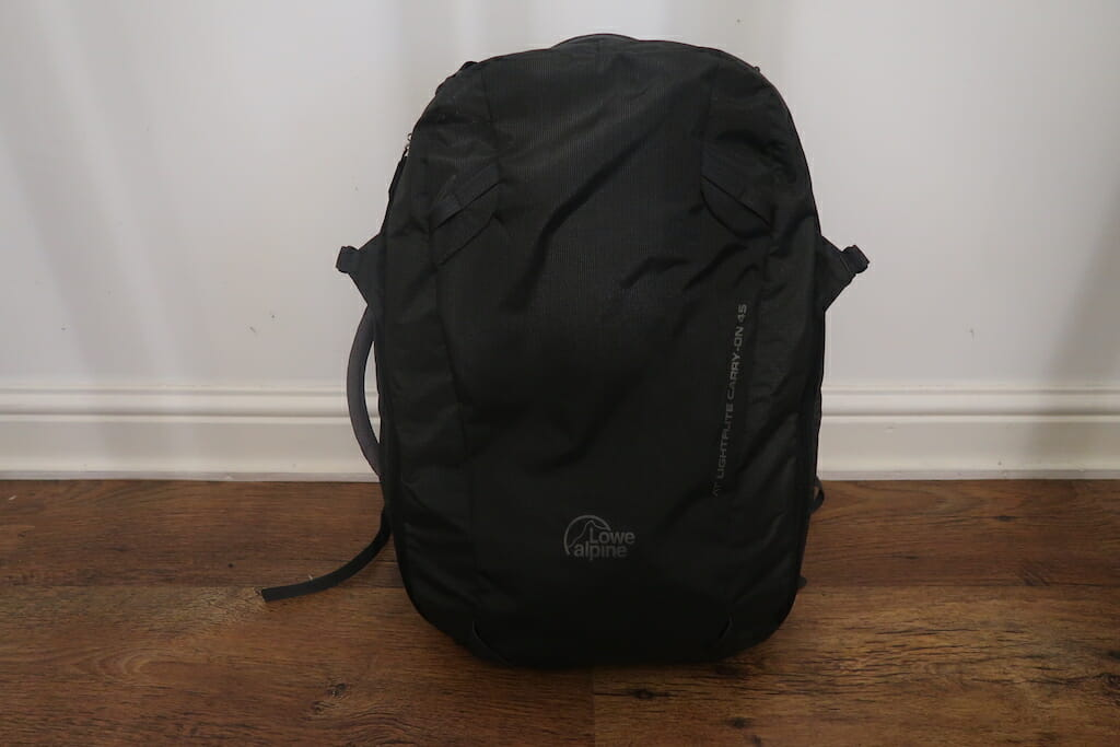 Black carry on backpack resting against a white wall on a lovely wood floor