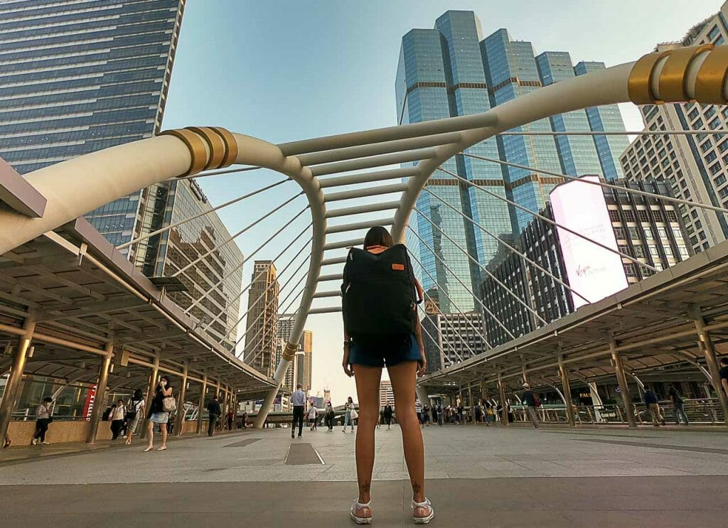 Woman, with her back facing the camera, walking across the bridge in a big city with a backpack on
