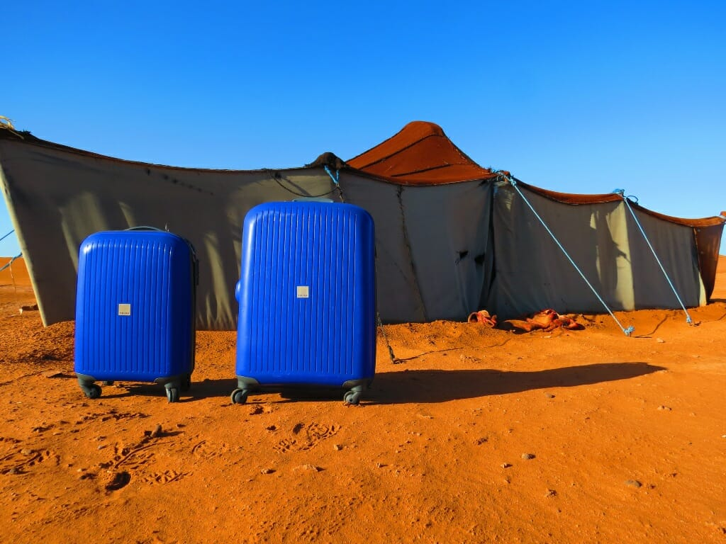 Two bright blue hard shell suitcases stark against the orange sand in front of a gray tent