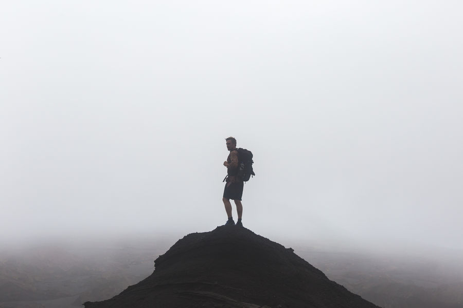 Silhouette of a man on a foggy peak with a backpack on