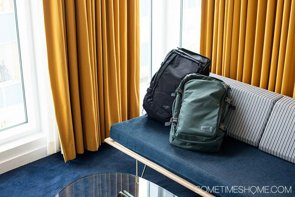 A teal bag leaning against a black bag on a gray and blue seat with yellow curtains behind it