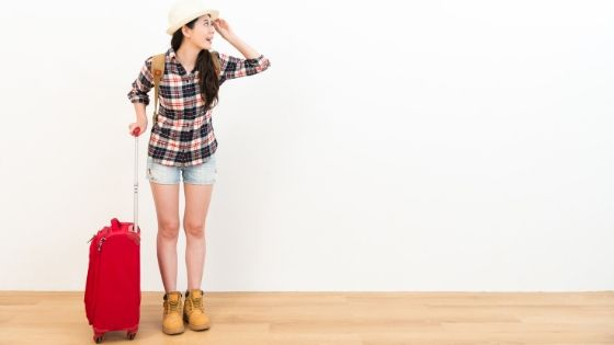 Woman standing in front of white wall with red carry on luggage