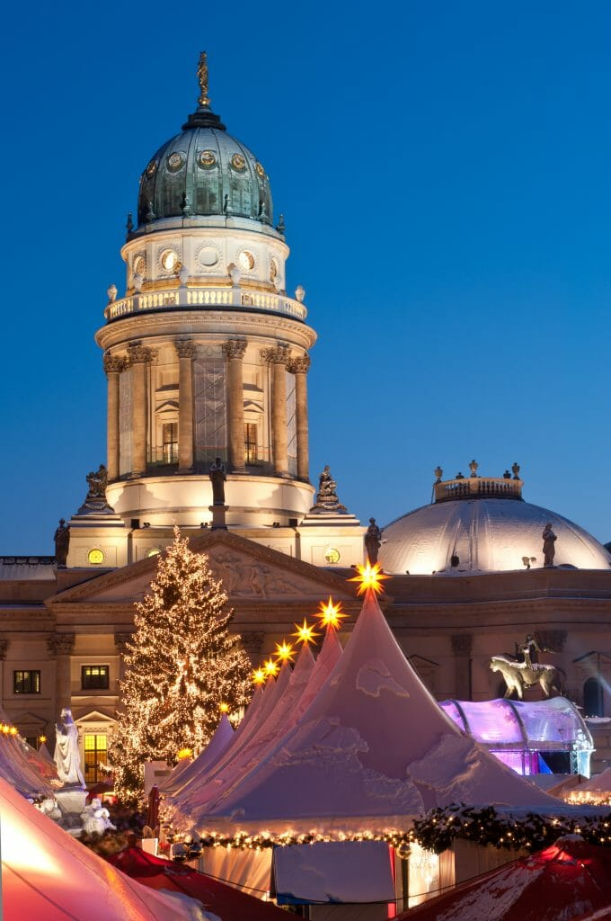 Snow covered white tents in front of a German cathedral in the evening surrounded by twinkling lights