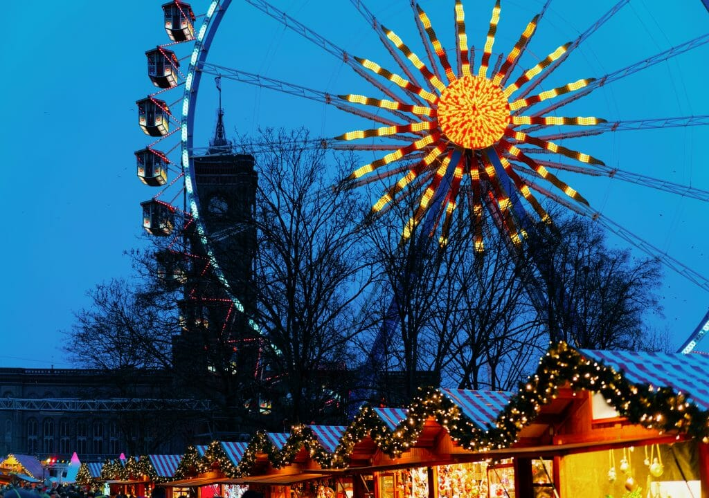 Ferris Wheel glowing above the Christmas market stalls at the Berlin Town Hall