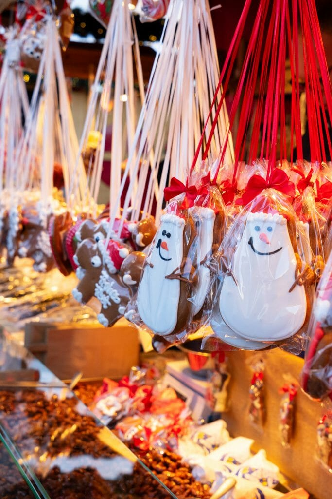 Gingerbread cookies decorated as snowmen hanging from a rod
