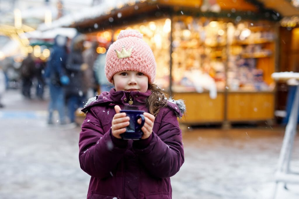 Little cute kid girl with cup of steaming hot chocolate or children punch. Happy child on Christmas market in Germany. Traditional leisure for families on xmas