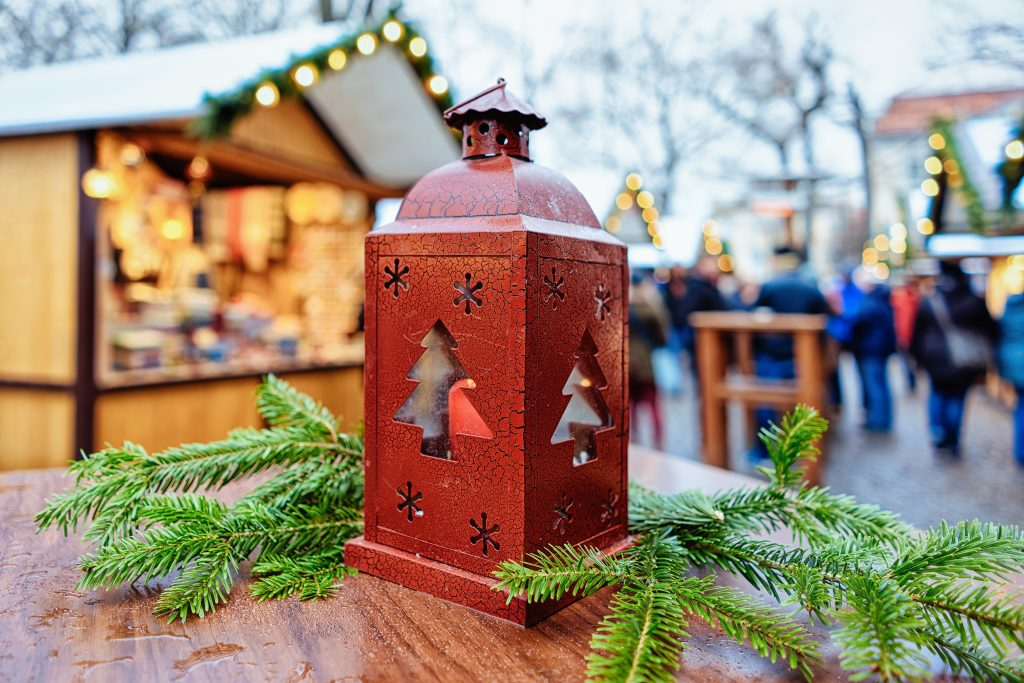 Lantern on a table surrounded by pine branches with the lively christmas market in the background