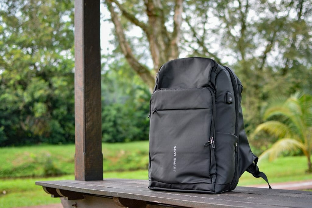 Black backpack sitting on a picnic table at the park during the day