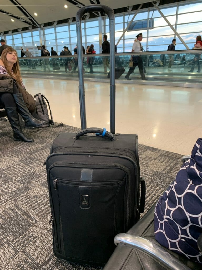 In a brightly lit airport with huge windows in the back, a black carry on suitcase awaits travel