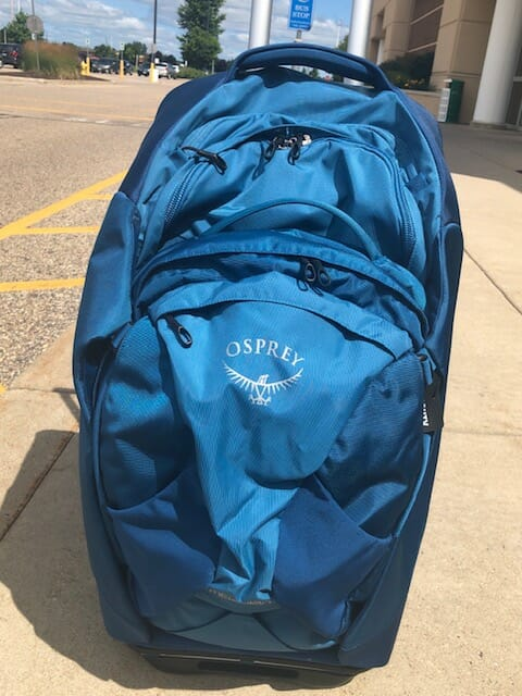 Bright blue backpack on a brightly light street during the daytime