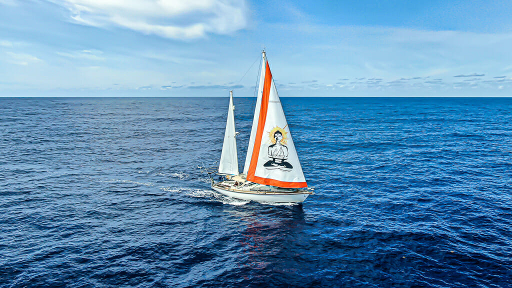SV Delos sail boat with white/orange sails with buddha image in the middle of the Atlantic.