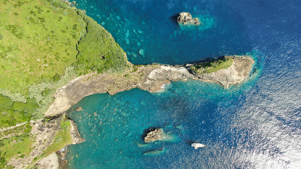 Aerial shot of turquoise water with rugged coastline and cliffs in Azores Islands