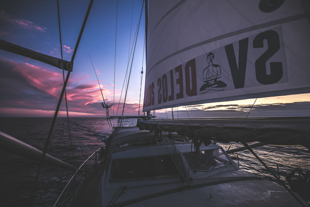 Sailboat SV Delos at sunset with pink/purple/blue sky and clouds