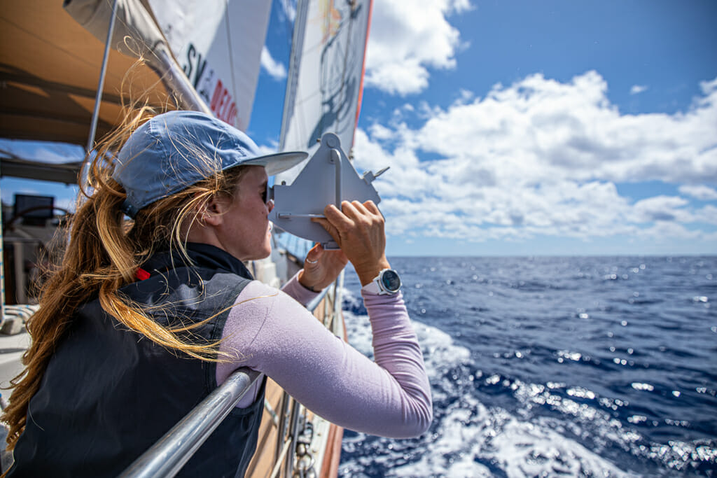 Woman on a sailboat using navigation device looking over the ocean