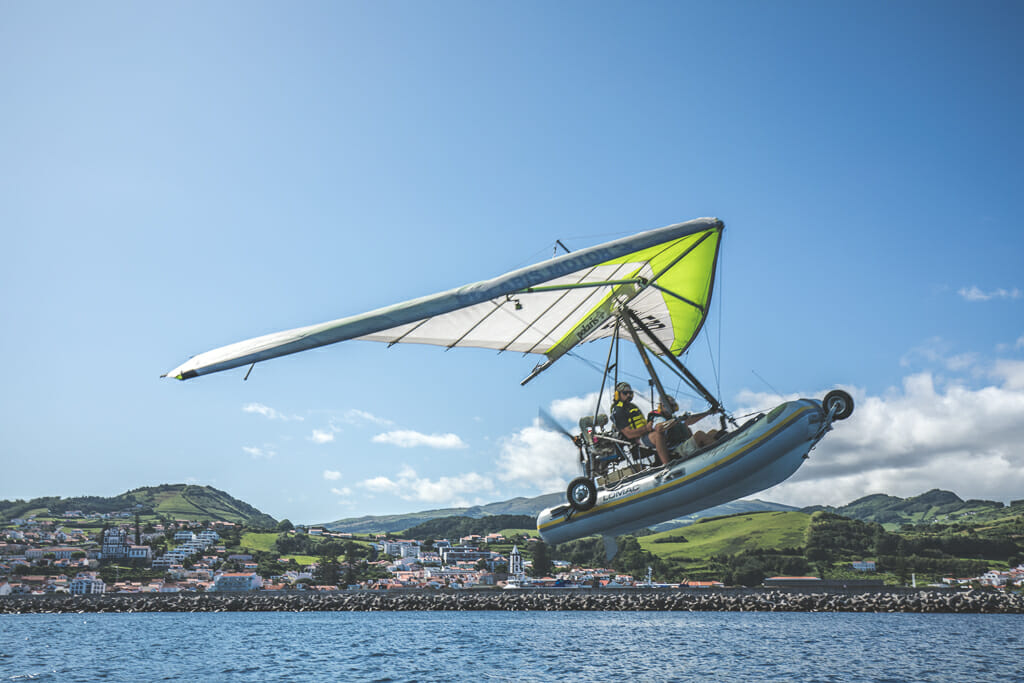 a Dinghy boat with a sail and motor flying over the coast line of Faial Island