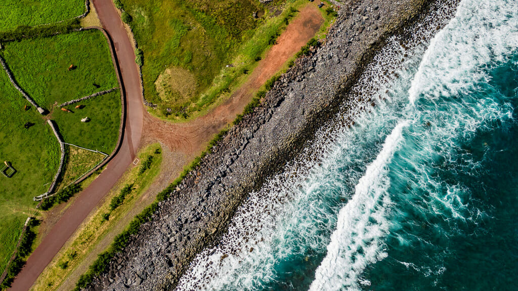 Aerial shot of green fields, rocky black beach and turquoise water with white foamy waves