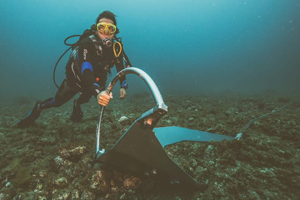Diver in full dive gear holding on to sail boat anchor under water