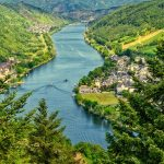 View of the Mosel river in Germany with boats sailing and vineyards being tended to while homes rest comfortably near the water